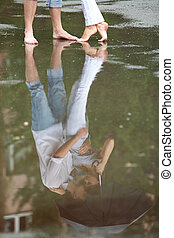 Puddle reflection - A couple hugging under umbrella...