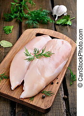 Raw chicken breasts prepared for cooking on wooden cutting...