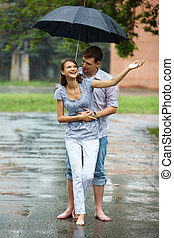Rainy day - A young couple walking in the rain barefoot
