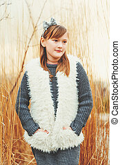 Outdoor portrait of cute 8-9 year old girl wearing grey...