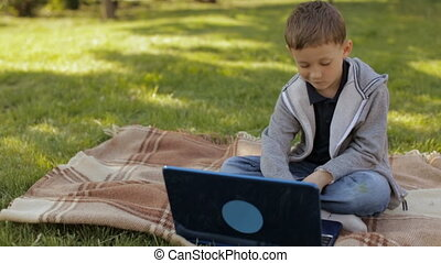 Boy with laptop outdoors,slow motion - Boy playing on laptop...