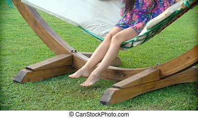 Woman legs swinging in hammock outdoors - Woman legs...
