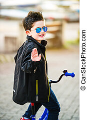 Little kid boy riding a bike, looking back over his...