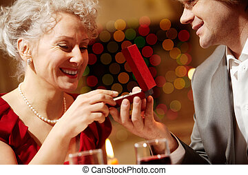 Offer - Photo of beautiful woman looking at ring in small...