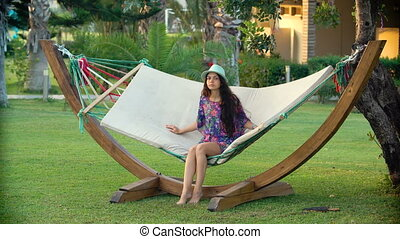 young smiling brunette woman in hat relaxed and Swinging in...