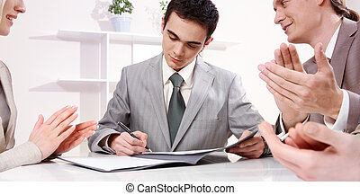 Signing a contract - A young businessman sitting at table...