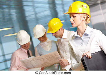 Young engineers - Three young engineers examining a project,...