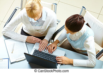 Businesswomen - Above view of two businesswomen typing on a...