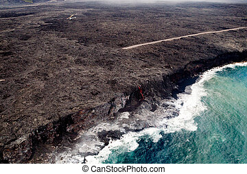 Lava flowing into the sea - Aerial shot of red glowing lava...