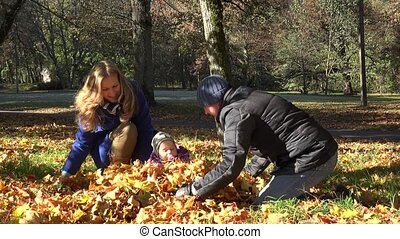 happy family with baby play with autumn leaves in garden. 4K