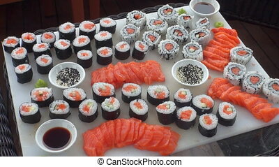 Sushi on a background of wooden floor and wicker furniture.