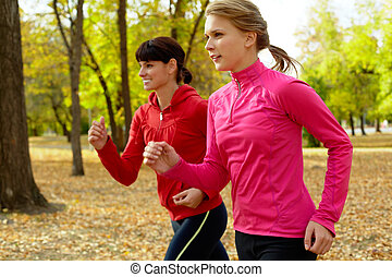Morning run - Two young women jogging in autumn park