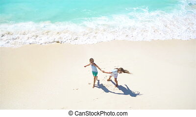 Adorable little kids play together on the beach at shallow water. View from above of a deserted beach with turquoise water