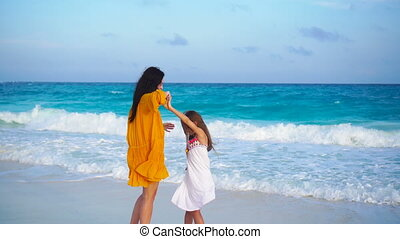 Little adorable girl and young mother at tropical beach in warm evening with beautiful sunset