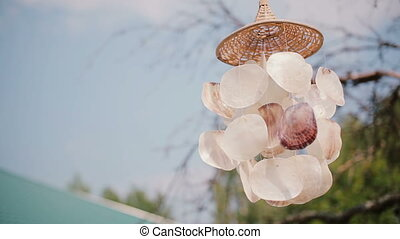 Close-up view of wind chime on a tree. Bright sunny day,...