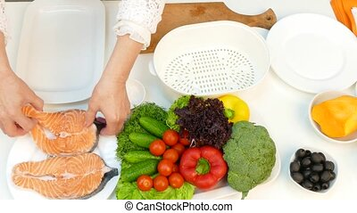 Preparation of salmon in a double boiler. - A woman is...