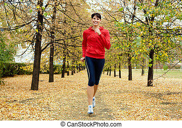 Jogger - Girl running among autumn trees and smiling