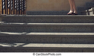 young girl with sneakers descends the stairs in slow motion