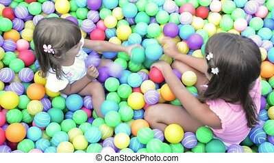 Baby girls in ball pool - Happy children playing in colored...
