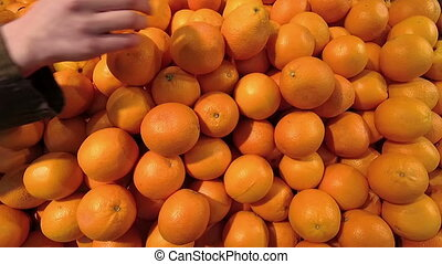 person buys oranges in the market. Hand close-up.