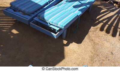 sand and beach loungers with bungalows near the Sea close-up