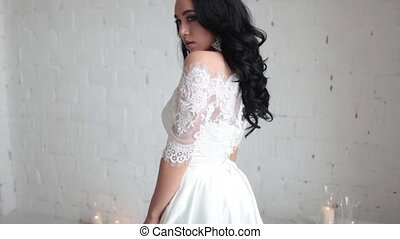 Tanned beautiful brunette bride in white wedding dress sitting on the chair. In the hands holding the cotton branches