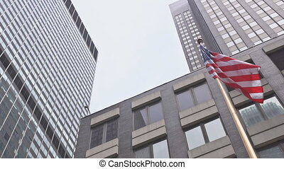 American flag waving against two skyscrapers and a blue sky.
