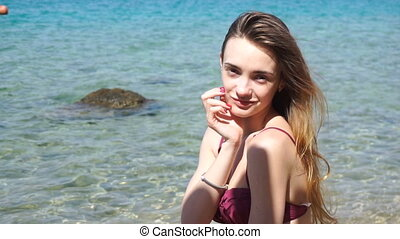 cute young girl with long hair stands near the sea smiles and looks into the camera