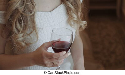 Young business woman relaxing at her hotel bedroom Drinks from a glass of red wine at the window. in luxurious room interior. Young beautiful girl in white dress
