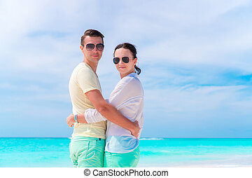Young couple on white beach during summer vacation. Happy...