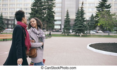 Dolly shot of Two attractive mixed race women with shopping bags talking and walking down the street. Girlfriends have fun after visiting mall sale