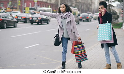Two attractive african american women with shopping bags calling for taxi cab while coming back from mall sales