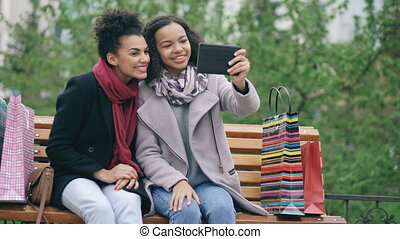 Two cheerful african american women with shopping bags having video call with tablet computer. Young friends sitting on bench have online chat