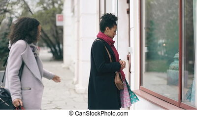 Two attractive mixed race women with shopping bags surpisely meet on the street near mall store