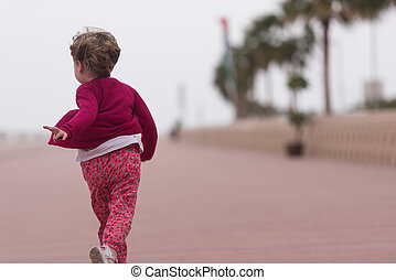 cute little girl on the promenade by the sea