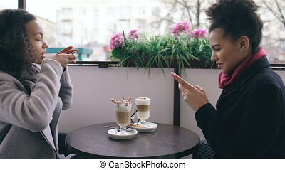 Two attractive mixed race female friends photographing coffee cups together using smartphone camera while sitting in street cafe outdoors