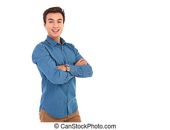 young casual man with hands folded posing in studio on white...