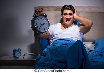 Man having trouble sleeping in bed