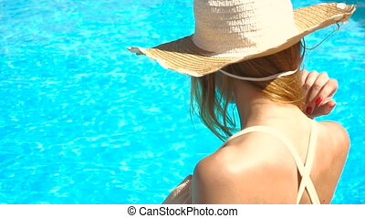 a young girl wearing a hat and glasses sit around the pool...
