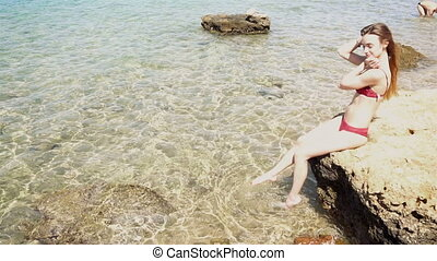 girl in red swimsuit sits on the rock and Flops feet in the...