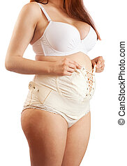 pregnant woman dressing maternity girdle - Closeup of...