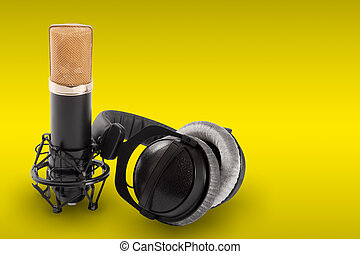 Headphones and condenser microphone on the yellow...