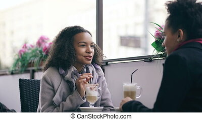 Two attractive mixed race women talking and drinking coffee in street cafe. Friends have fun after visiting mall sale
