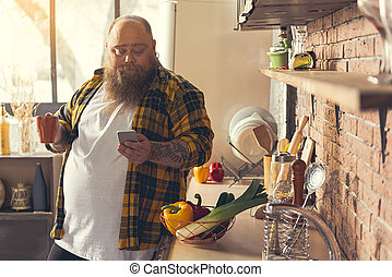 Relaxed fat man enjoying hot drink at home - Lazy thick guy...