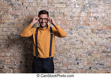 Laughing male wearing suspenders and orange polo neck -...