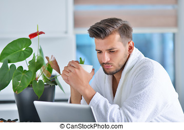 Handsome young man drinking coffee while working with laptop...
