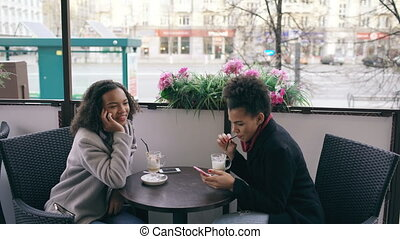Attrcative mixed race woman sitting at the table in the street cafe talking cell phone while her friend surfing smartphone