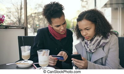 Two attractive mixed race women having online shopping with credit card and smartphone while talking and drinking coffee in street cafe