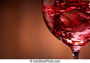 Close-up of brightly red wine poured in the wineglass and...