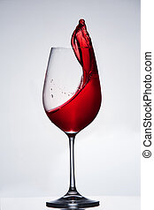 Splashing and moving red wine in the pure wineglass standing...